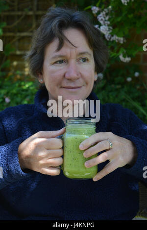 Woman holding a green vegetable smoothie, seated outdoors. - Stock Photo