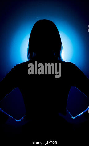 Silhouette of female with back to camera and hands on hips against blue spot lit background - Stock Photo