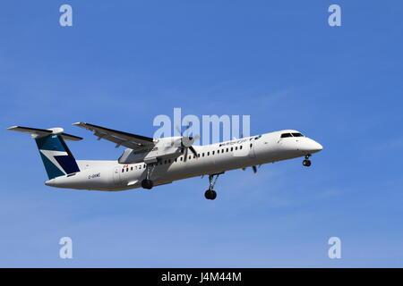 Bombardier Dash-8 preparing to land at the Montreal Pierre Elliott Trudeau International airport - Stock Photo