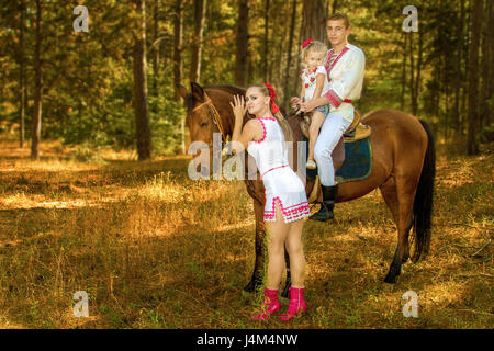 Ukrainians Mom and Dad and daughter in the woods with a horse - Stock Photo