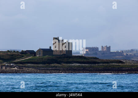 St Cuthbert's Chapel and Castell's Tower on Inner Farne Island, and Bamburgh Castle, on the coast of Northumberland - Stock Photo