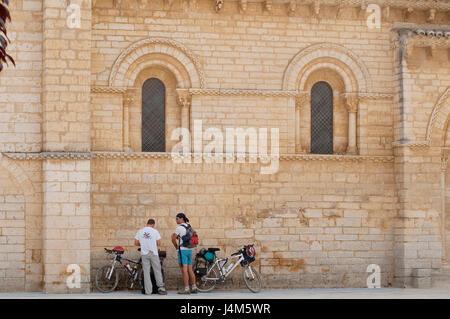 Two pilgrims at San Martin church. Camino de Santiago, Fromista, Palencia province, Castilla Leon, Spain. - Stock Photo