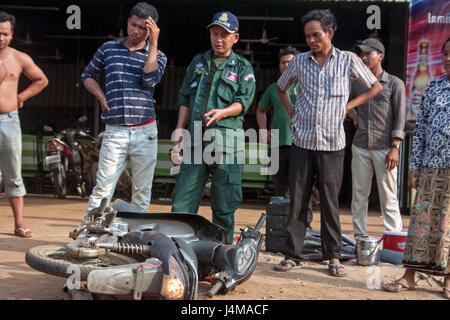 A policeman points to a motorcycle as people are gathered at the scene of an accident in Chork village, Tboung Khmum - Stock Photo