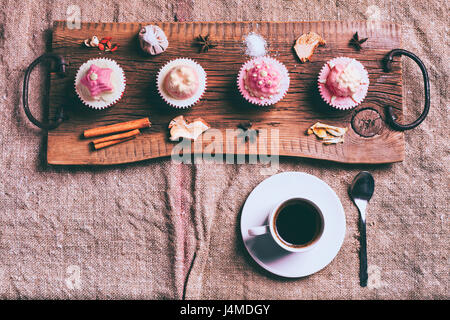 Cupcakes on ingredients on wooden tray with coffee - Stock Photo