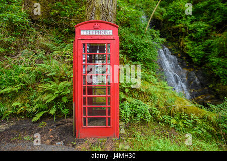 Red telephone box in the forest next to a waterfall. Scotland, United Kingdom - Stock Photo