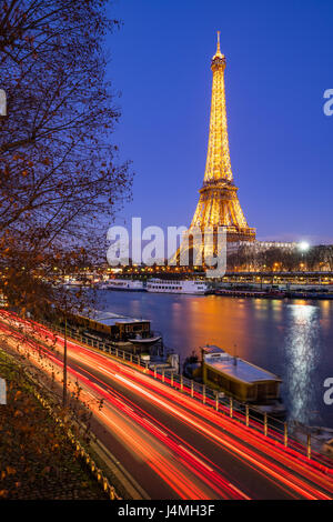 Eiffel Tower illuminated at twilight and Seine River, Paris - Stock Photo