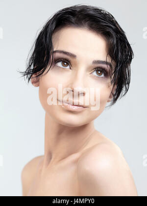 Beautiful young woman relaxed fresh face with big brown eyes and short dark hair. Beauty headshot on gray studio - Stock Photo