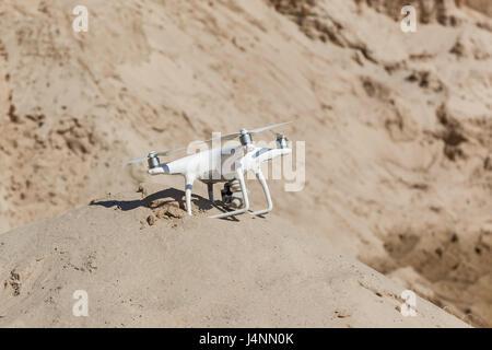 Ukraine, Kyiv 25 april 2017 white quadcopter sat down on a sandy hill - Stock Photo