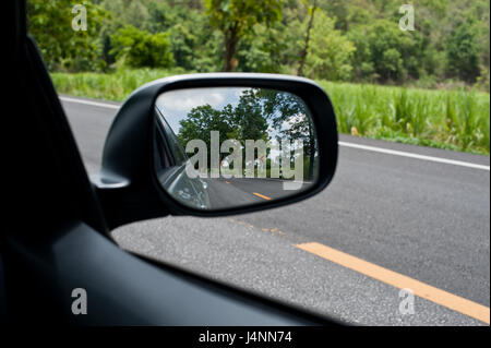 Landscape in the sideview mirror of a car, on road countryside, natural - Stock Photo