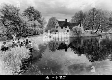 Infra Black and White Picture of Willie Lott's Cottage in Constable Country Showing School Groups Visiting - Stock Photo