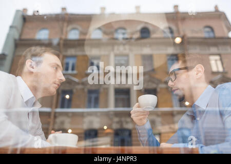 Side view portrait of two businessmen sitting at opposite sides of table in cafe discussing deal during meeting, - Stock Photo