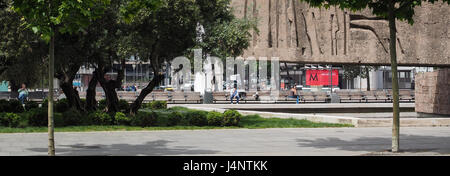 a view through under sculpture to peole sitting on bench in park Gardens of Discovery Jardines des Descubrimiento - Stock Photo