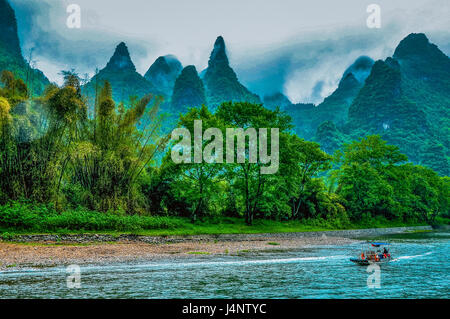 Karst mountains and Li River scenery in the mist - Stock Photo