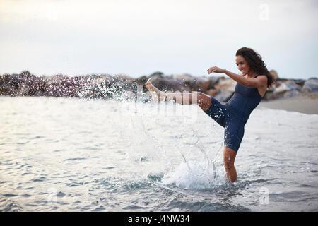 A female triathlete on the beach wearing her triathlon suit - Stock Photo