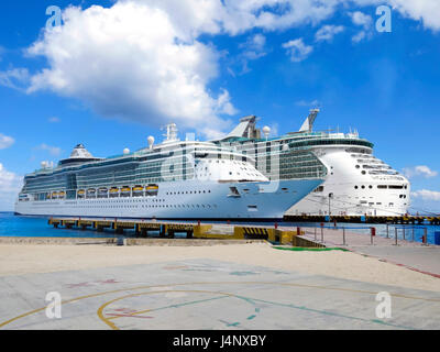 Two Cruise Ships tied together on one pier with blue water and sky - Stock Photo