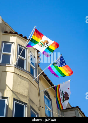 A rainbow Mexican flag, rainbow American flag, and rainbow California flag hanging from a window of a building in - Stock Photo