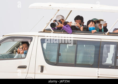Asian Tourists With Cameras In Open Roof 4x4 Safari Vehicle, Maasai Mara, Kenya - Stock Photo