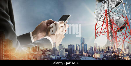 Businessman using smartphone with double exposure modern cityscape in sunrise, and telecommunication towers - Stock Photo