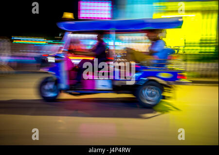 A classic motorised tuk-tuk taxi zooms by in a night blur of neon lights in Bangkok, Thailand - Stock Photo