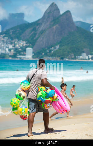RIO DE JANEIRO - FEBRUARY 10, 2017: A beach vendor selling colorful beach balls and toys carries his display along - Stock Photo