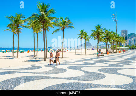 RIO DE JANEIRO - FEBRUARY 15, 2017: A couple walk together along the iconic black and white wave pattern of the - Stock Photo
