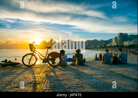 People sit watching the sunset at Arpoador, a popular summertime activity for locals and tourists, in Rio de Janeiro, - Stock Photo