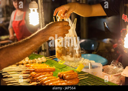 CHIANG MAI, THAILAND - AUGUST 21: Man buys meatballs at the Sunday Market (Walking Street) on August 21, 2016 in - Stock Photo