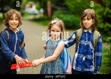 Little school students on the schoolyard. Three friends schoolmates. The girl and two boys with satchels behind - Stock Photo