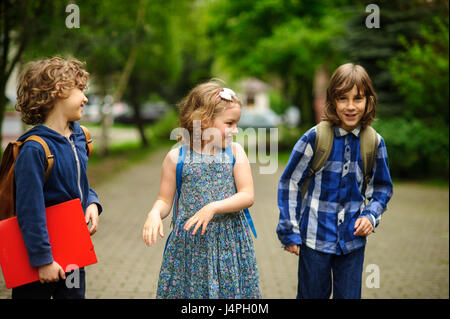 Little school students have started a game on the schoolyard. Two boys and the girl have fun waiting for the beginning - Stock Photo