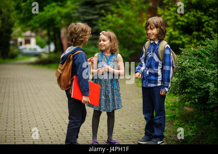 Little school students briskly and cheerfully talk on the schoolyard. Two boys and the girl have fun waiting for - Stock Photo