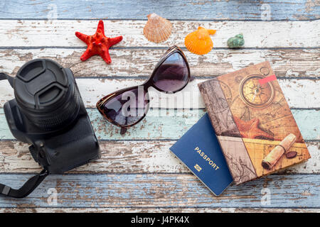 Travel concept: seashells, sunglasses, passport and journal on vintage table - Stock Photo