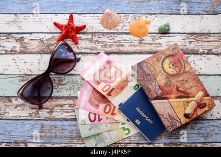 Travel concept: seashells, sunglasses, passport, money and journal on vintage table - Stock Photo