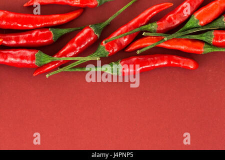 red hot chili peppers, popular spices concept - close-up on a beautiful handful of red hot pepper pods scattered - Stock Photo