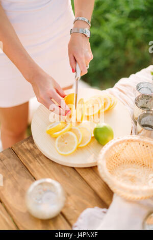 picnic, people, food, summer, holiday concept - young slender woman in a white dress with a knife cut green lime - Stock Photo
