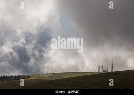 Some antennas on top of a mountain with a wall of clouds and fog - Stock Photo