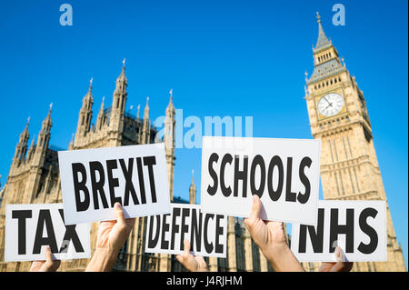 Election signs protesting modern British social issues like Brexit, tax, education, defense, health at the Houses - Stock Photo
