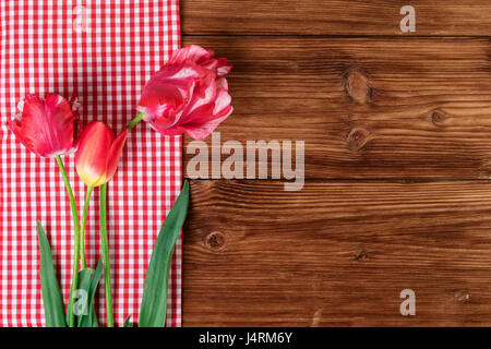 Tulips with red checkered tablecloth on country wooden background. Top view, text space - Stock Photo