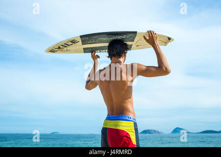 RIO DE JANEIRO - FEBRUARY 5, 2017: A young Brazilian stands scanning for waves with his skimboard overhead on Ipanema - Stock Photo