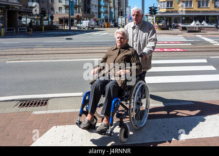 Retired husband with disabled elderly wife in wheelchair traversing street over pedestrian crossing / crosswalk - Stock Photo