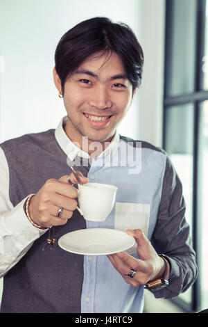 asian younger man toothy smiling face with hot coffee cup in hand - Stock Photo