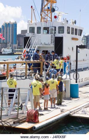 Group of Cub Scouts boarding the USCG ship Ahi for a tour. Honolulu Harbor, Oahu, Hawaii, USA - Stock Photo