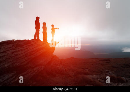 Family of tourists staying on the edge of the cliff against the backdrop of an incredible mountain landscape. Evening - Stock Photo