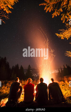 Four friends sitting near campfire in high mountains. Amazing night scene. Man friendship concept - Stock Photo