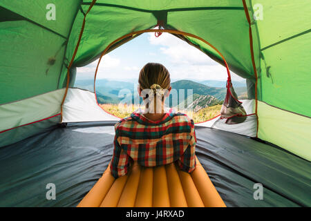Girl sitting in they tent against the backdrop of an incredible mountain landscape. Sunny day in highland - Stock Photo