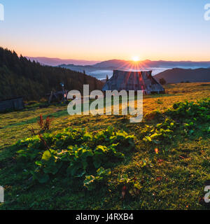 Shepherd house in high mountain. Orange sunrice glowing by sunlight. Summer time in highland - Stock Photo