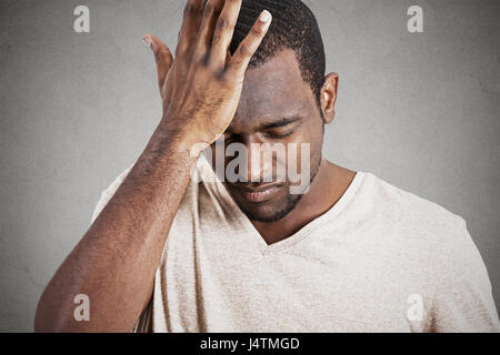 Closeup headshot very sad depressed, stressed, alone, disappointed gloomy young man head on hands having suicidal - Stock Photo