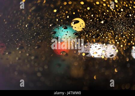 Raindrops on window grass at night - Stock Photo