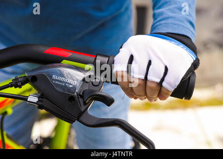 Tambov, Russian Federation - May 07, 2017 Child hand with glove on handlebars with Shimano speed shift and brake - Stock Photo
