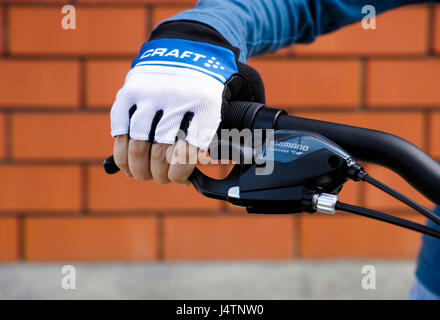 Tambov, Russian Federation - May 07, 2017 Child hand with Craft glove on handlebars with Shimano brake lever. - Stock Photo