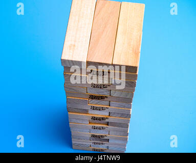Tambov, Russian Federation - March 03, 2016 Jenga blocks in tower constructed on blue background. Studio shot. - Stock Photo